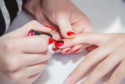 Paint lacquer red nails in beauty salon body care